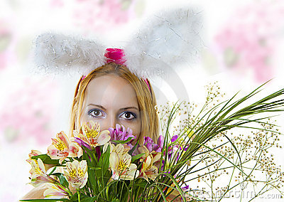 Easter bunny female looking over flowers