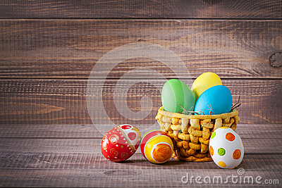 Easter color eggs in basket on wood