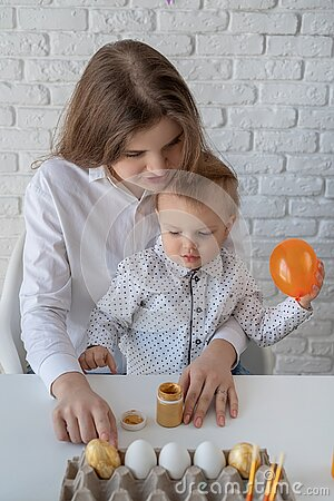 Mother and her little son learning to paint easter eggs Stock Photo