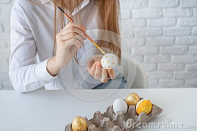 Young woman coloring eggs for Easter at home Stock Photo