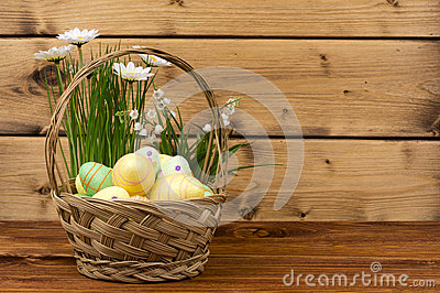 Easter decoration - basket with eggs, flowers on wooden background. Stock Photo