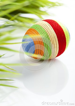 Easter egg with colored wool around it.