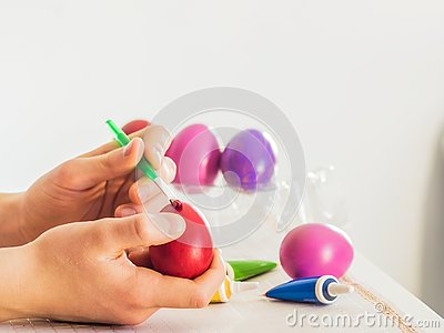 Easter egg coloring process with a brush of acrylic paints, hand action on a white table on a white background of the room Stock Photo