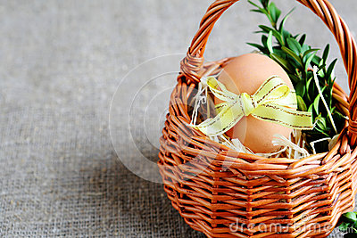 Easter egg with yellow ribbon in a basket
