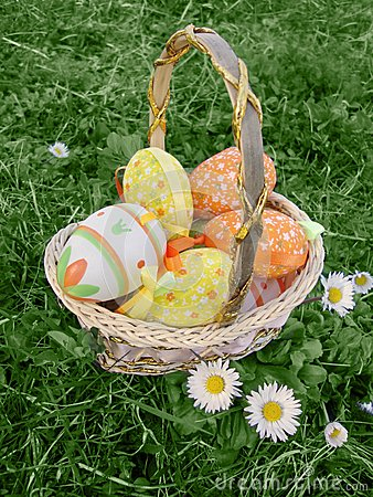 Easter eggs in basket on grass Stock Photo