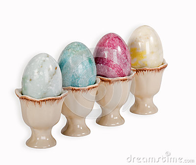 Easter eggs in egg cups over white