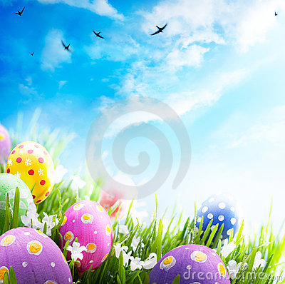 Easter eggs with flowers in grass on blue sky