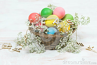 Easter eggs with flowers over bright wooden background Stock Photo