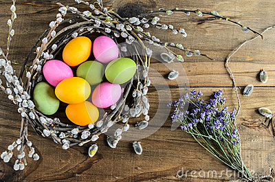 Easter eggs in willow nest, flowers over wooden rustic background Stock Photo
