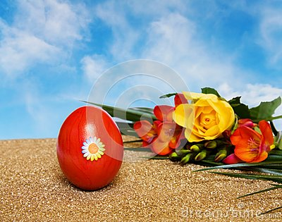 Easter red decorated egg and flowers over blue sky