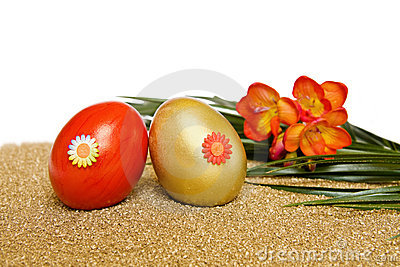 Easter red and golden eggs with freesia flower