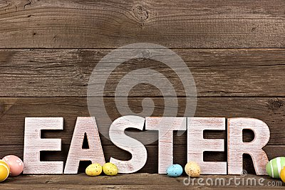 easter spelled in white wooden letters with easter eggs on a rustic wooden background