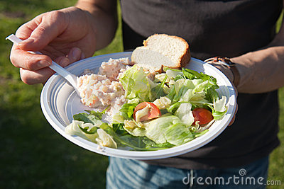 Eating a fresh salad during a picnic party
