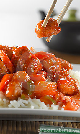 Eating sweet and sour chicken with chopsticks