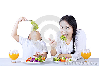 Eating vegetables with mother on white