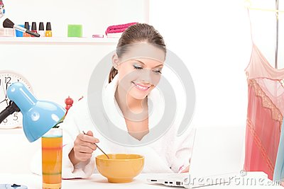 Eating woman with laptop computer