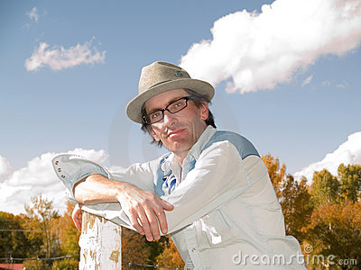 Eccentric man leaning to a fence post
