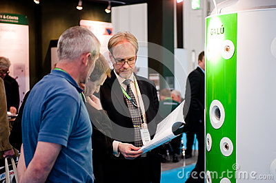 An exhibitor shows a product brochure to potential Editorial Stock Image