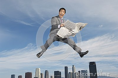 Ecstatic Businessman Holding A Newspaper