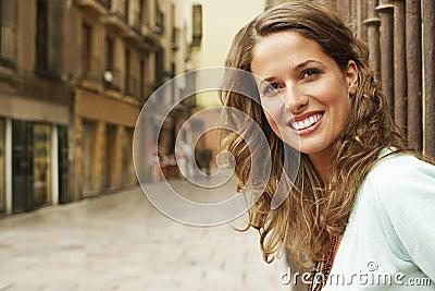 Edificios exteriores derechos sonrientes de la mujer en calle