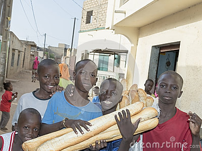 Editorial caption: Thiaroye, Senegal, Africa – July 28, 2014: Unidentified children (bread delivery boys) in the street