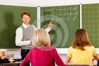 Education - Teacher with pupil in school teaching