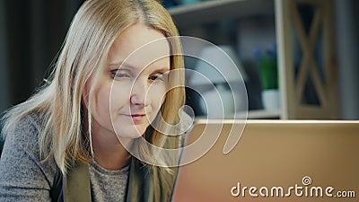 Een aantrekkelijke vrouw van middelbare leeftijd werkt met een laptop in haar kamer stock videobeelden