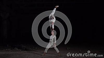 Een acrobat staat op de ene arm, de andere houdt hem op zijn hoofd stock footage