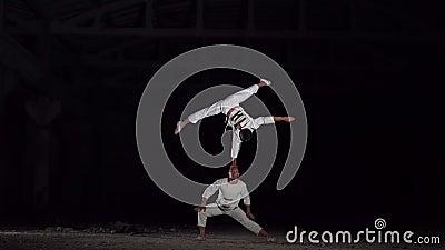 Een acrobat staat op de ene arm, de andere houdt hem op zijn hoofd stock video
