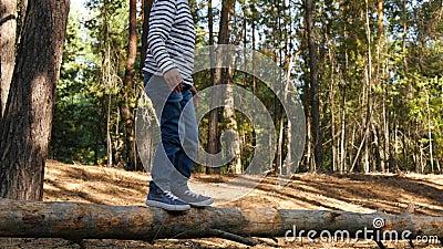 Een actieve jongen loopt op een straal om obstakels te overwinnen Kindertijd en ontwikkeling stock videobeelden