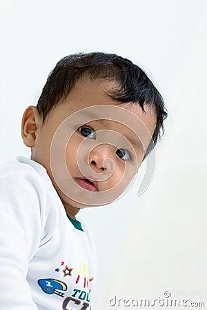 Een baby die aan camera staart.