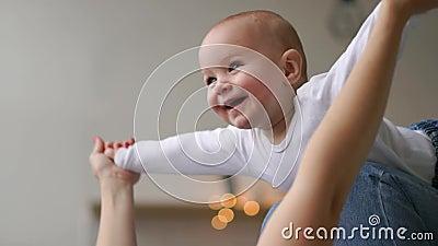Een baby in een witte t-shirt ligt op de overlapping die van zijn moeder de vlucht van een vliegtuig imiteren stock videobeelden