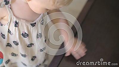 Een babymeisje in de zomer die globaal het TV-scherm onderzoeken stock video