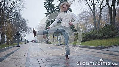 Een befaamde jonge blanke jongen in een elegant wit shirt, vest, en een vlechtige dasje dansen in het stadspark Funny Kauasian stock video