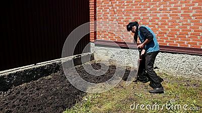 Een bejaarde, met een vod op zijn hoofd, die met een schop, in zonnig weer graven stock video