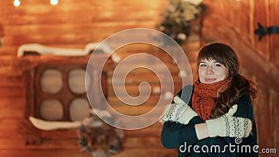 Een bevroren meisje in vuisthandschoenen verwarmt zich op de achtergrond van een houten sprookjehuis Kerstmis en Nieuwjaarthema stock footage
