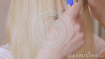 Een blonde vrouw met lang haar kamt voor een spiegel, voorbereidend haar hoofd voor het kleuren van haarwortels stock footage