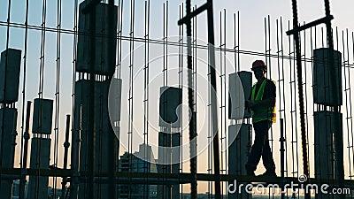 Een bouwer werkt met metaalconstructies op een bouwplaats stock videobeelden