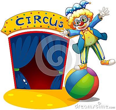 Een clown bij de bovenkant van de bal naast een circushuis
