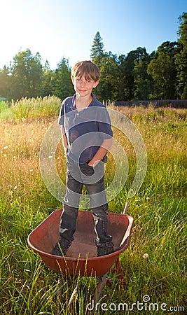Een echte jonge jongen die zich in een kruiwagen bevinden