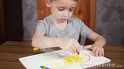 Een gelukkig glimlachend leuk kind trekt met kleurpotloden of een potlood terwijl thuis het zitten bij een lijst De ontwikkeling  stock videobeelden