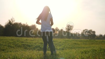 Een gelukkig meisje loopt in de armen van haar liefhebbende moeder Het geluk van moederschap, vriendschap, vertrouwen, liefde stock videobeelden