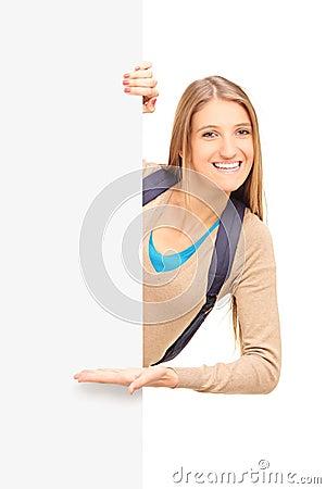 Een glimlachende vrouwelijke student die op een paneel gesturing