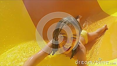 Een grappig meisje rijdt op een oranje dia op haar maag stock videobeelden