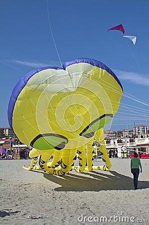 Een grote gele vlieger in de blauwe hemel op het strand