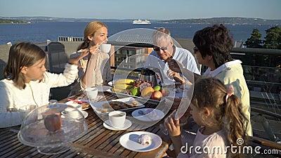 Een grote gelukkige familie heeft diner op het open terras op het dak van het huis stock footage