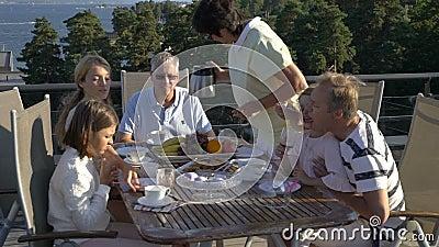 Een grote gelukkige familie heeft diner op het open terras op het dak van het huis stock video