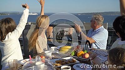 Een grote gelukkige familie heeft diner op het open terras en de golven zijn handen die door de overzeese veerboot overgaan stock footage