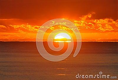 Een halve zon toont over oceaan bij zonsopgang