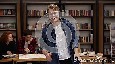 Een handige, opgewonden europese man met een denim-shirt met expressieve dans terwijl hij naar favoriete muziek luistert stock video